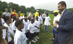 In this Aug. 1, 2000 photo, Elnardo Webster, Director of Summer Youth Development Program, gives a pep talk to the kids before the Lacrosse clinic of the school district's new Summer Youth Development Program Activities at West Side Park in Newark, N.J. Soon after Cory Booker became mayor of Newark, Webster, his former campaign aide and law partner, authored a November 2006 memo recommending new watershed board members. The memo, written on law firm letterhead that still listed Booker as a partner, advised the mayor to appoint a businessman who had played college football with Webster. (William Perlman/NJ Advance Media via AP)