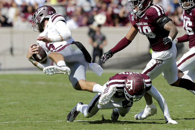 Mississippi State quarterback Garrett Shrader (6) is taken of his feet by Texas A&M defensive back Debione Renfro (29) after a short run during the second half of an NCAA college football game, Saturday, Oct. 26, 2019, in College Station, Texas. (AP Photo/Sam Craft)