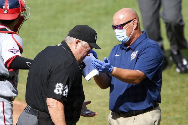 Home plate umpire Joe West (22) is tended to by a Washington Nationals trainer after he was injured during the first inning of a baseball game between the Toronto Blue Jays and the Nationals, Thursday, July 30, 2020, in Washington. (AP Photo/Nick Wass)