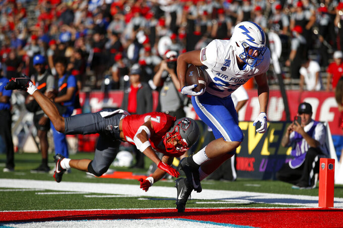 Air Force wide receiver Dane Kinamon (23) scores a touchdown against New Mexico safety Tavian Combs (7) during the first half of an NCAA college football game on Saturday, Oct. 2, 2021, in Albuquerque, N.M. (AP Photo/Andres Leighton)