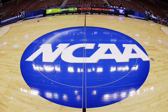 FILE - In this March 21, 2013, file photo taken with a fisheye lens, the NCAA logo is displayed at mid-court before Albany's practice for a second-round game of the NCAA college basketball tournament in Philadelphia. A judge has ruled against the NCAA in a federal antitrust lawsuit, saying football and basketball players should be permitted to receive more compensation from schools but only if the benefits are tied to education. (AP Photo/Matt Slocum, File)