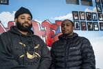 Darren Neal, left, and Jason Page stand in front of wall of photos showing community members who have died from causes such as gun violence and drug overdoses inside of the Truce Center in St. Paul, Minn., on Thursday, Jan. 9, 2020. The two came to the Truce Center to resolve a misunderstanding before it could have potentially turned violent. (Evan Frost/Minnesota Public Radio via AP)