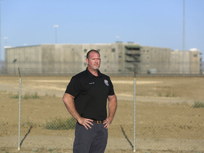 Aaron McGlothin, union president at the Federal Correctional Institution at Mendota, stands in front of the prison during a protest against staffing shortages, near the prison entrance in Mendota, Calif., Monday, May 17, 2021. (AP Photo/Gary Kazanjian)