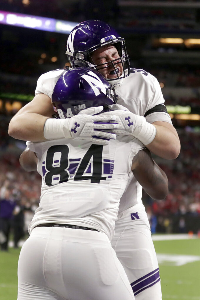 Northwestern wide receiver Cameron Green (84) celebrates a touchdown with teammate Trey Klock during the second half of the Big Ten championship NCAA college football game against Ohio State, Saturday, Dec. 1, 2018, in Indianapolis. (AP Photo/Michael Conroy)