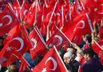 FILE - In this file photo dated Monday, July 15, 2019, people waving Turkish flags gather for a rally to honour the victims of the July 15, 2016 failed coup attempt, in Istanbul.  Turkey's combative president Recep Tayyip Erdogan enjoys widespread popular support within Turkey. (AP Photo/Lefteris Pitarakis, FILE)