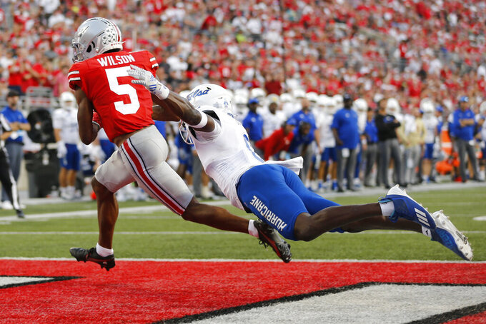 Ohio State receiver Garrett Wilson, left, catches a touchdown in front of Tulsa linebacker Brian Johnson during the second half of an NCAA college football game Saturday, Sept. 18, 2021, in Columbus, Ohio. (AP Photo/Jay LaPrete)