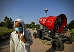 A man wearing a mask as a precaution against the coronavirus walks past an anti-smog gun kept at the Central Park in New Delhi, India, Monday, Oct.5, 2020. Authorities in New Delhi launched an anti-pollution campaign on Monday in an attempt to curb air pollution levels ahead of winter, when the capital is regularly covered in toxic haze, and warned that filthy air could make the coronavirus pandemic more dangerous. (AP Photo/Manish Swarup)