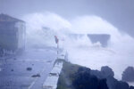 Waves crash on a seafront road in Horta, in the Portuguese island of Faial, Wednesday, Oct. 2, 2019. Hurricane Lorenzo lashed the mid-Atlantic Azores Islands with heavy rain, powerful winds and high waves Wednesday, but initial reports said it caused only minor damage. (AP Photo/Joao Henriques)
