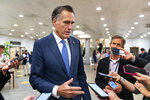 Sen. Mitt Romney, R-Utah, speaks to reporters as he walks on the Senate subway on Capitol Hill, Tuesday, June 8, 2021, in Washington. (AP Photo/Manuel Balce Ceneta)