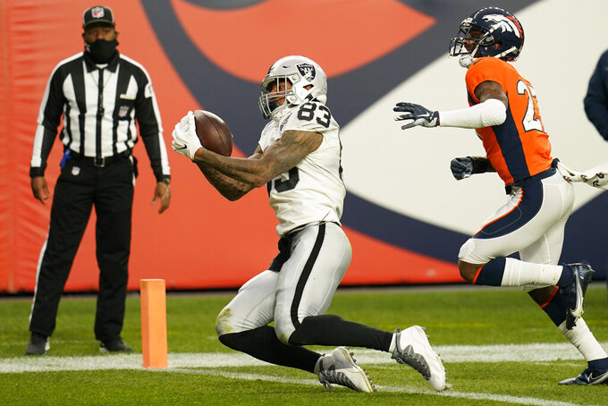 Las Vegas Raiders tight end Darren Waller (83) catches a touchdown pass against Denver Broncos strong safety Will Parks (27) during the first half of an NFL football game, Sunday, Jan. 3, 2021, in Denver. (AP Photo/Jack Dempsey)