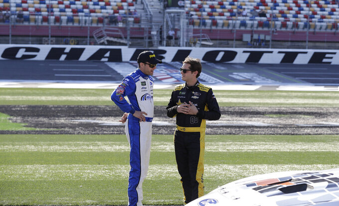 David Ragan, left, talks with Landon Cassill before qualifying for Saturday's NASCAR All-Star Cup series auto race at Charlotte Motor Speedway in Concord, N.C., Friday, May 17, 2019. (AP Photo/Chuck Burton)
