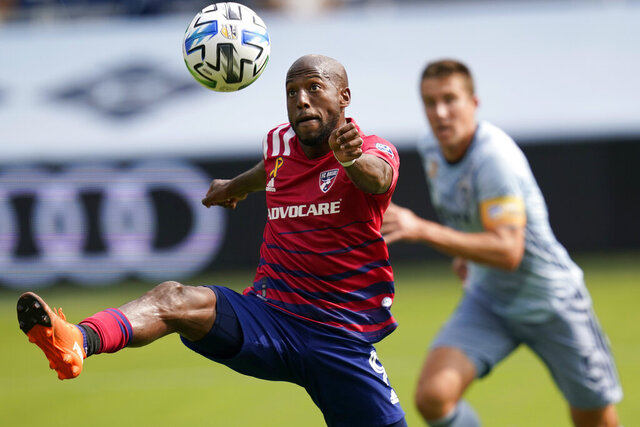 FC Dallas forward Fafa Picault (9) controls the ball in front of Sporting Kansas City defender Matt Besler (5) during the first half of an MLS soccer match in Kansas City, Kan., Saturday, Sept. 19, 2020. (AP Photo/Orlin Wagner)