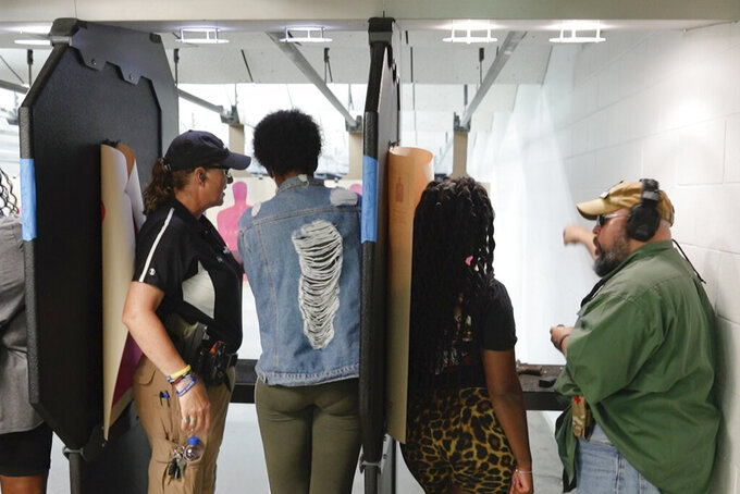 In this Aug. 21, 2021, image taken from video, firearms instructors, left, and right, teach female customers on the shooting range at the Recoil Firearms store in Taylor, Mich. About 1,000 or so mostly Black women took part in free weekend gun safety and shooting lessons at two Detroit-area ranges. Black women increasingly are considering gun ownership for personal protection, according to industry experts and gun rights advocates. (AP Photo/Carlos Osorio)