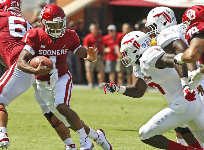 Oklahoma quarterback Kyler Murray (1) scrambles as Florida Atlantic linebacker Rashad Smith (7) moves in at right in the first half of an NCAA college football game in Norman, Okla., Saturday, Sept. 1, 2018. (AP Photo/Sue Ogrocki)