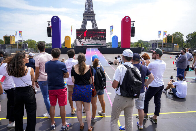 People watch on a giant screen the opening ceremony of the 2020 Summer Olympics in Tokyo, at the Trocadero gardens next to the Eiffel Tower in Paris, Friday, July 23, 2021. (AP Photo/Michel Euler)