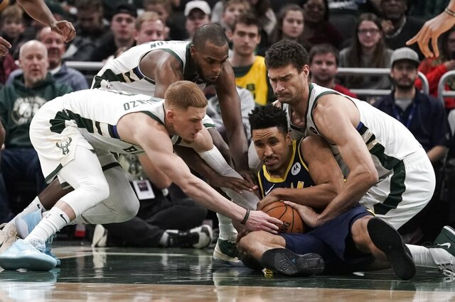Indiana Pacers' Malcolm Brogdon battles for a loose ball with Milwaukee Bucks' Donte DiVincenzo, Khris Middleton and Brook Lopez during the second half of an NBA basketball game Sunday, Dec. 22, 2019, in Milwaukee. The Bucks won 117-89. (AP Photo/Morry Gash)
