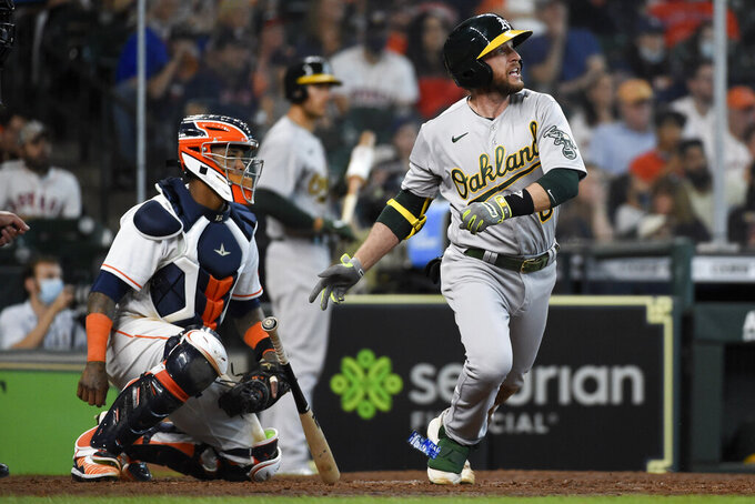 Oakland Athletics' Jed Lowrie, right, watches his two-run single during the seventh inning of a baseball game against the Houston Astros, Saturday, April 10, 2021, in Houston. (AP Photo/Eric Christian Smith)