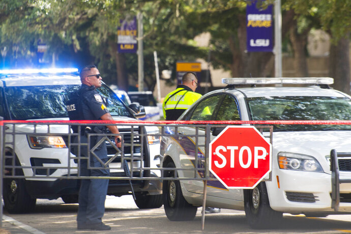 Law enforcement personnel stand with weapons near two LSU police vehicles parked in between the LSUU Student Union and Coates Hall, in New Orleans after the all-clear on a possible armed intruder in Coates Hall, Tuesday, August 20, 2019.  (Travis Spradling/The Advocate via AP)
