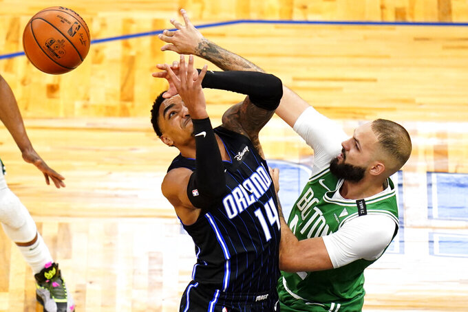 Boston Celtics guard Evan Fournier, right, knocks the ball from the hands of Orlando Magic guard Gary Harris (14) during the first half of an NBA basketball game, Wednesday, May 5, 2021, in Orlando, Fla. (AP Photo/John Raoux)