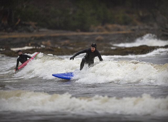 Husband and wife Nick and Jaimie-lee Mitchell surf on Sunday, Dec. 6, 2020, at Rotary Beach in Ketchikan, Alaska. Ongoing storms have provided groups of surfers the opportunity to catch waves this holiday season. (Dustin Safranek/Ketchikan Daily News via AP)