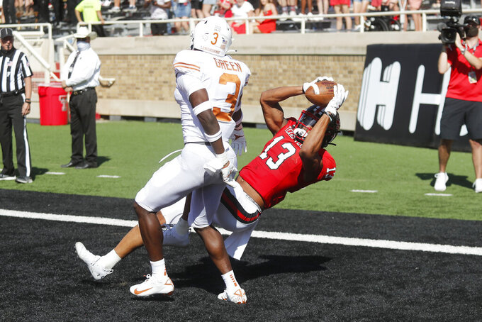 Texas Tech wide receiver Erik Ezukanma makes a diving catch in the end zone for a touchdown covered by Texas defensive back Jaklen Green during the first half of an NCAA college football game against Texas Tech, Saturday Sept. 26, 2020, in Lubbock, Texas. (AP Photo/Mark Rogers)