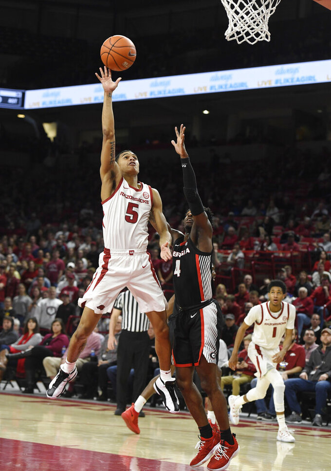 Arkansas guard Jalen Harris (5) drives past Georgia defender Tyree Crump (4) during the first half of an NCAA college basketball game, Tuesday, Jan.29, 2019 in Fayetteville, Ark. (AP Photo/Michael Woods)