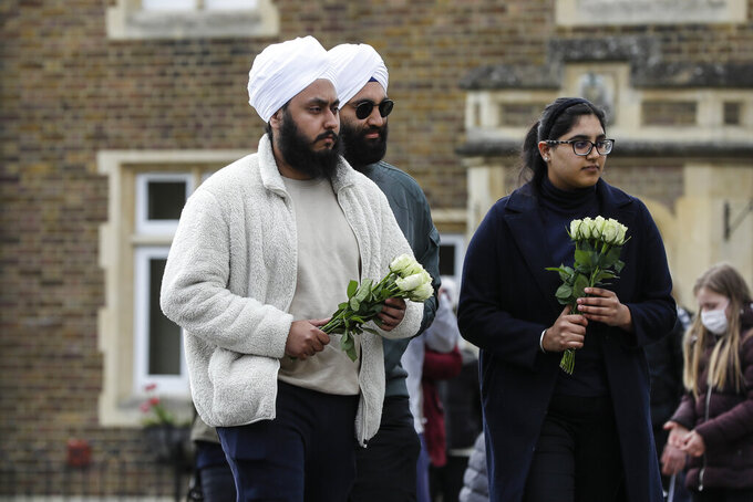 Members of the public bring flowers to Windsor Castle in Windsor, England after the announcement regarding the death of Britain's Prince Philip, Friday, April 9, 2021. Buckingham Palace officials say Prince Philip, the husband of Queen Elizabeth II, has died. He was 99. Philip spent a month in hospital earlier this year before being released on March 16 to return to Windsor Castle. (AP Photo/Kirsty Wigglesworth)