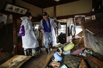 Toshio Yonezawa, 73, center, surveys his home with son, Yusuke, after Typhoon Hagibis passed through his neighborhood Tuesday, Oct. 15, 2019, in Nagano, Japan. More victims and more damage have been found in typhoon-hit areas of central and northern Japan, where rescue crews are searching for people still missing. (AP Photo/Jae C. Hong)