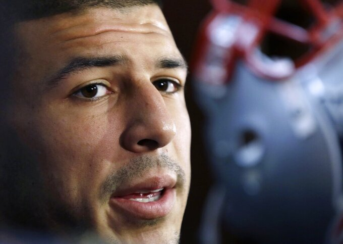 "HOLD FOR STORY BY WILLIAM J. KOLE — FILE - In this Sept. 5, 2012 file photo, New England Patriots tight end Aaron Hernandez speaks in the locker room at Gillette Stadium in Foxborough, Mass. More than two years after he hanged himself in his prison cell in April 2017, while serving a life sentence for a 2013 murder, Netflix is releasing ""Killer Inside: The Mind of Aaron Hernandez"" on Jan. 15, 2020. Hernandez's suicide came just a days after he was acquitted of most charges in another double murder case. (AP Photo/Elise Amendola, File)"