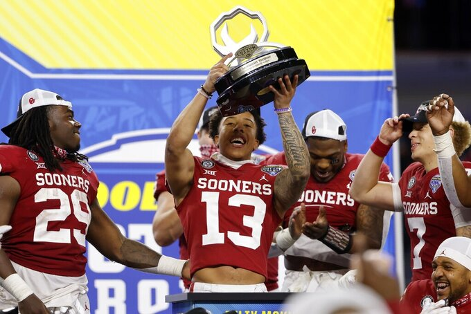 Oklahoma defensive back Tre Norwood (13) celebrates after being named the outstanding defensive player trophy in the team's Cotton Bowl NCAA college football game against Florida in Arlington, Texas, Wednesday, Dec. 30, 2020. (AP Photo/Michael Ainsworth)