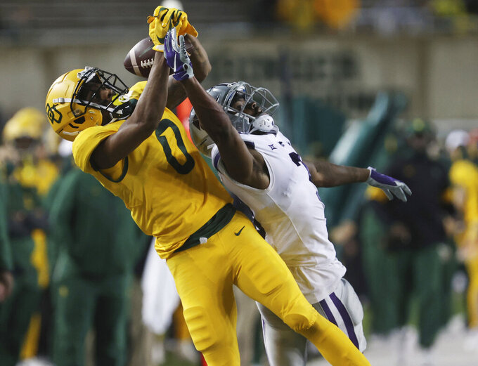 FILE- In this Nov. 28, 2020, file photo, Baylor wide receiver R.J. Sneed, left, pulls in a long pass over Kansas State defensive back Kiondre Thomas, right, in the second half of an NCAA college football game in Waco, Texas. Senior receiver R.J. Sneed said there is a different feel with team chemistry going into 2021, nearly 20 months after Dave Aranda was hired as head coach. (Rod Aydelotte/Waco Tribune-Herald via AP, File)