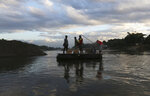 Locals cross the Suchiate River from Mexico to Guatemala with boxes of eggs, near Ciudad Hidalgo, Chiapas state, Mexico, Friday, Jan. 17, 2020. United States officials are crediting tough measures taken over the past year and cooperation from regional governments for sharply reducing the number of Central American migrants who responded to a call for a new caravan. (AP Photo/Marco Ugarte)