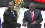 FILE - In this Wednesday, May 22, 2013 file photo Zimbabwean President Robert Mugabe, left, shakes hands with Prime Minister Morgan Tsvangirai after he signed the new constitution into law at State house in Harare. On Friday, Sept. 6, 2019, Zimbabwe President Emmerson Mnangagwa said his predecessor Robert Mugabe, age 95, has died. (AP Photo/Tsvangirayi Mukwazhi, File)