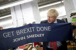 Britain's Prime Minister Boris Johnson hold a scarf with slogan