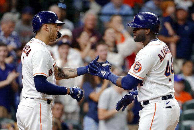 Houston Astros Carlos Correa, left, and Yordan Alvarez (44) celebrate Alvarez's home run during the seventh inning of the team's baseball game against the Texas Rangers on Saturday, July 24, 2021, in Houston. (AP Photo/Michael Wyke)