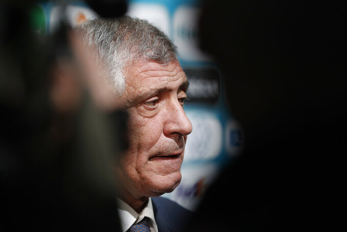 FILE - In this file photo dated Saturday, Nov. 30, 2019, Portugal coach Fernando Santos talks to journalists after the draw for the UEFA Euro 2020 soccer tournament finals in Bucharest, Romania. Coach Fernando Santos will remain in charge of Portugal national soccer team until the 2024 European Championship, the Portuguese soccer federation said Tuesday June 16, 2020. (AP Photo/Petr David Josek, FILE)