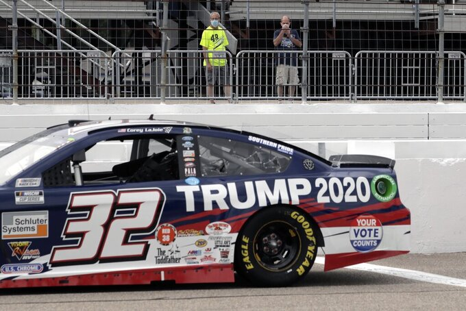 Fans view the car of NASCAR driver Corey LaJoie (32), bearing wording to support the re-election bid of President Donald Trump, before a NASCAR Cup Series auto race, Sunday, Aug. 2, 2020, at the New Hampshire Motor Speedway in Loudon, N.H. (AP Photo/Charles Krupa)