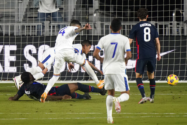 U.S. forward Ayo Akinola, on ground, scores a goal against El Salvador during the first half of an international friendly soccer match Wednesday, Dec. 9, 2020, in Fort Lauderdale, Fla. (AP Photo/Wilfredo Lee)