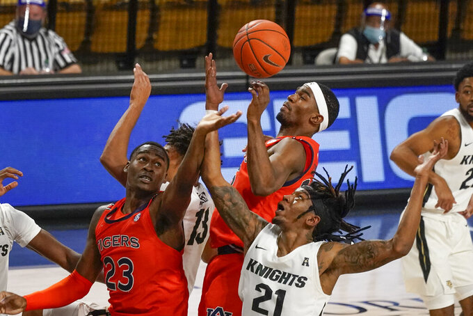 Auburn forward Jaylin Williams (23) and guard Devan Cambridge, center, battle Central Florida forward C.J. Walker (21) for a rebound during the second half of an NCAA college basketball game, Monday, Nov. 30, 2020, in Orlando, Fla. (AP Photo/John Raoux)