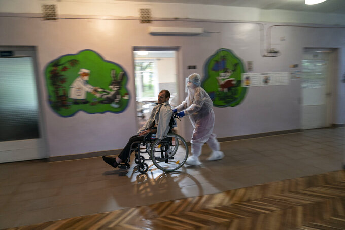 A nurse transports a patient with COVID-19 in a wheelchair at a hospital in Stebnyk, Ukraine, on Wednesday, Sept. 30 2020. As coronavirus cases increase, every bed in the hospital in this city in western Ukraine is in use and its chief doctor is watching the surge with alarm and anguish. (AP Photo/Evgeniy Maloletka)