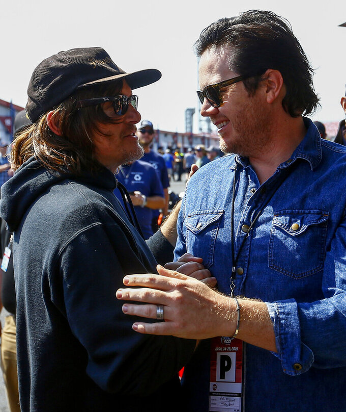 Actors Norman Reedus and Josh McDermitt, right, of the Walking Dead talk in the garage area before the Geico 500 at Talladega Superspeedway, Sunday, April 28, 2019, in Talladega, Ala. (AP Photo/Butch Dill)