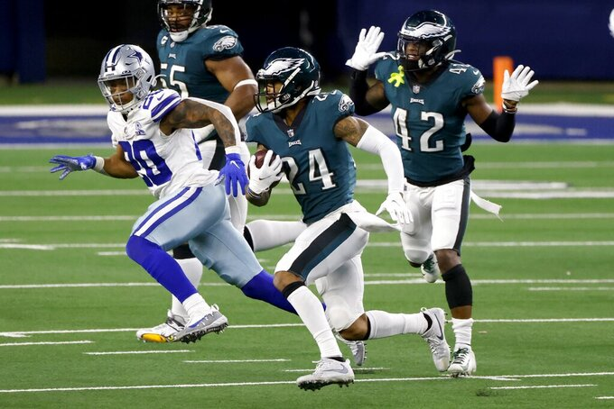Philadelphia Eagles cornerback Darius Slay (24) intercepts a Dallas Cowboys quarterback Andy Dalton pass as Dallas Cowboys running back Tony Pollard (20) moves to make the stop in the second half of an NFL football game in Arlington, Texas, Sunday, Dec. 27. 2020. The Eagles' K'Von Wallace (42) and Brandon Graham, rear, look on during the play. (AP Photo/Ron Jenkins)