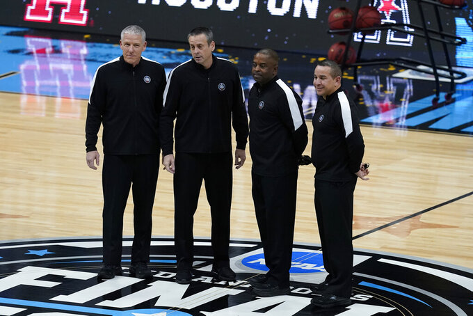 Game officials pose for a photo on the court before a men's Final Four NCAA college basketball tournament semifinal game between Baylor and Houston, Saturday, April 3, 2021, at Lucas Oil Stadium in Indianapolis. (AP Photo/Darron Cummings)