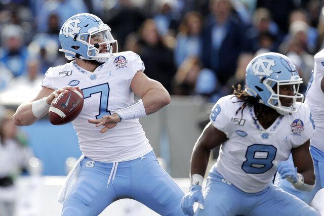 FILE - North Carolina quarterback Sam Howell throws a touchdown pass to wide receiver Dyami Brown during the first half of the Military Bowl NCAA college football game against Temple, Friday, Dec. 27, 2019, in Annapolis, Md. No. 18 North Carolina has plenty of hype with quarterback Sam Howell leading an offense full of returning playmakers for Mack Brown's second season. The Tar Heels open Saturday against Syracuse with a chance to prove the hype is deserved. (AP Photo/Julio Cortez, File)