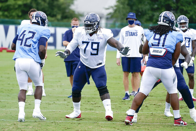 FILE - In this Friday, Aug. 28, 2020, file photo, Tennessee Titans offensive tackle Isaiah Wilson (79) runs a drill during NFL football training camp in Nashville, Tenn. A person familiar with the deal said Monday, March 8, 2021, that the Tennessee Titans have traded offensive lineman Wilson to the Miami Dolphins in a move unloading their first-round draft pick after his rookie season. (AP Photo/Mark Humphrey, Pool, File)