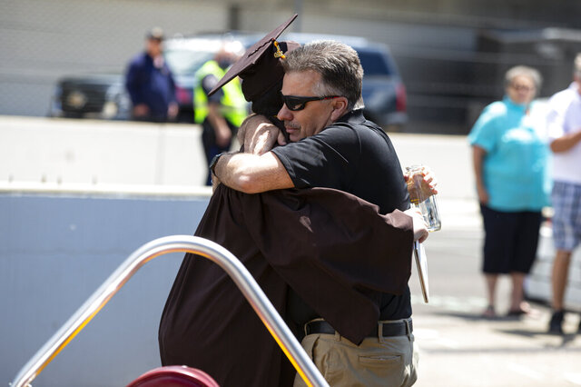 Ted Foxworthy, right, hugs his son Jacob Foxworthy as they walked off the track where he received his Speedway High School diploma during a ceremony at the Indianapolis Motor Speedway in Indianapolis, Saturday, May 30, 2020. The ceremony was held at the track to allow for social distancing requirements due to the COVID-19 pandemic. When Ted Foxworthy was diagnosed with cancer, he set two goals: Celebrating his youngest child's 18th birthday and seeing him graduate. (AP Photo/Michael Conroy)