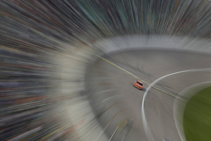 In this photo taken with a slow shutter, Daniel Suarez drives during a NASCAR Cup Series auto race at Kansas Speedway in Kansas City, Kan. Sunday, Oct. 20, 2019. (AP Photo/Charlie Riedel)