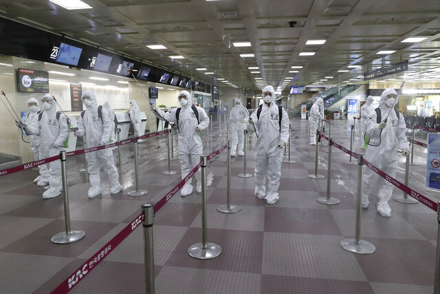 FILE - In this March 6, 2020, file photo, South Korean army soldiers wearing protective suits spray disinfectant to prevent the spread of the new coronavirus at Daegu International Airport in Daegu, South Korea. As cases of the coronavirus surge in Italy, Iran, South Korea, the U.S. and elsewhere, many scientists say it's plain that the world is in the grips of a pandemic — a serious global outbreak.  (Kim Joo-sung/Yonhap via AP)