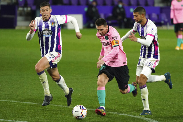 Barcelona's Lionel Messi, centre, runs past Real Valladolid's Ruben Alcaraz, right during a Spanish La Liga soccer match between Valladolid and Barcelona at the Jose Zorrilla stadium in Valladolid, Spain,Tuesday Dec. 22, 2020. (Cesar Manso/Pool via AP)