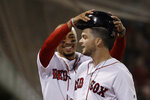 Boston Red Sox's Mookie Betts grabs the helmet from Andrew Benintendi, right, to celebrate the latter's solo home run against the Minnesota Twins during the eighth inning of a baseball game at Fenway Park, Tuesday, Sept. 3, 2019, in Boston. (AP Photo/Elise Amendola)